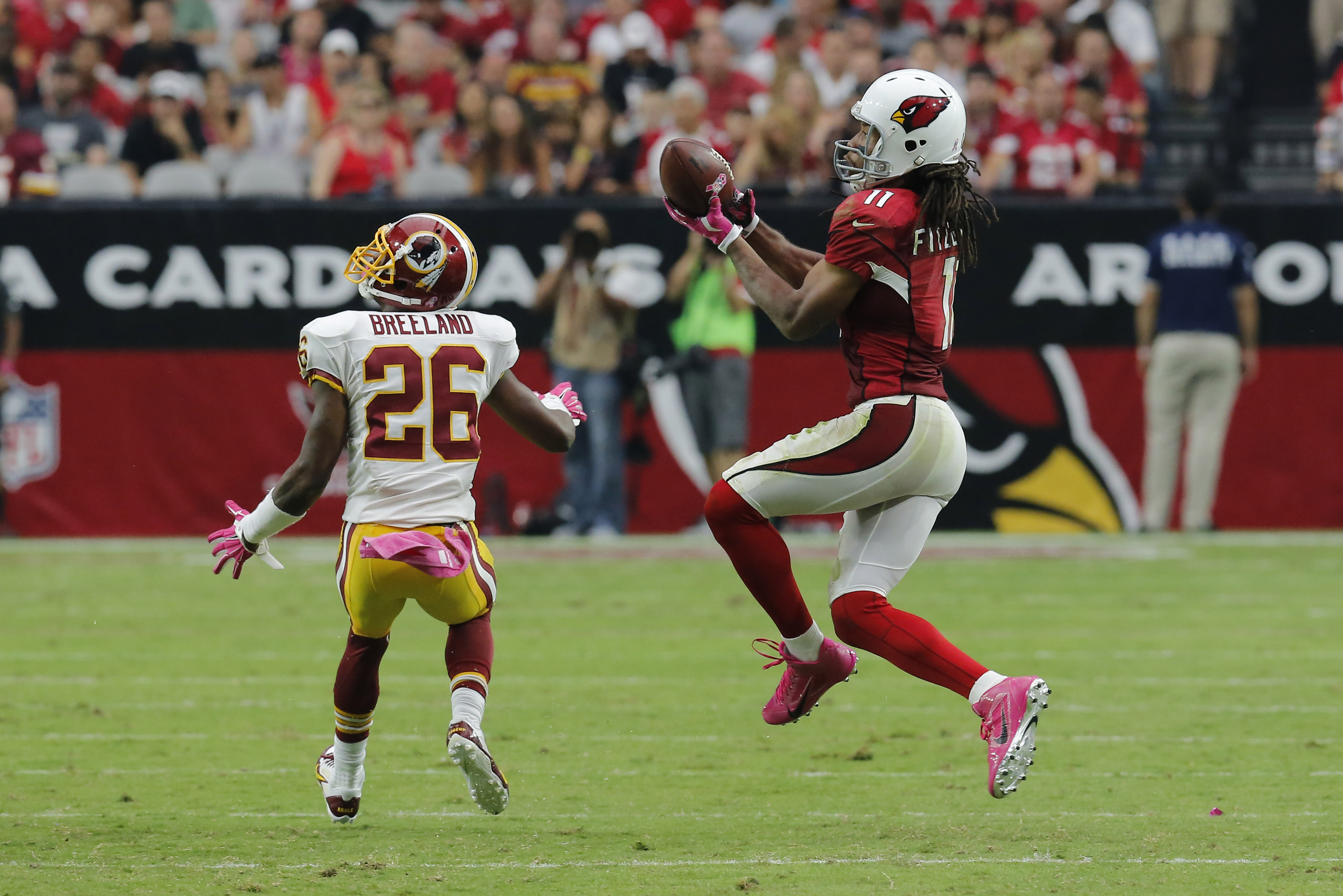 Arizona Cardinals wide receiver Larry Fitzgerald (11) pulls in a pass as Washington Redskins strong safety Bashaud Breeland (26) defends during the second half of an NFL football game, Sunday, Oct. 12, 2014, in Glendale, Ariz.(AP Photo/Rick Scuteri)